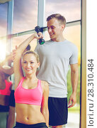 Купить «smiling young woman with personal trainer in gym», фото № 28310484, снято 29 июня 2014 г. (c) Syda Productions / Фотобанк Лори