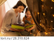 Купить «happy family reading book in kids tent at home», фото № 28310824, снято 27 января 2018 г. (c) Syda Productions / Фотобанк Лори