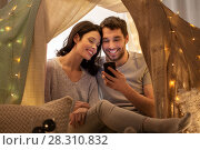 Купить «happy couple with smartphone in kids tent at home», фото № 28310832, снято 27 января 2018 г. (c) Syda Productions / Фотобанк Лори