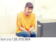 Купить «happy asian young woman watching tv at home», фото № 28310964, снято 9 марта 2016 г. (c) Syda Productions / Фотобанк Лори