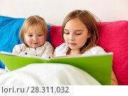 Купить «little girls or sisters reading book in bed», фото № 28311032, снято 15 октября 2017 г. (c) Syda Productions / Фотобанк Лори