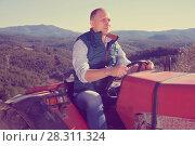 Купить «Confident male owner of vineyard driving tractor outdoors in sunny day», фото № 28311324, снято 22 января 2018 г. (c) Яков Филимонов / Фотобанк Лори