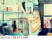 Купить «Portrait of young cheerful woman choosing earrings», фото № 28311348, снято 26 марта 2019 г. (c) Яков Филимонов / Фотобанк Лори