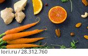 Купить «close up of carrot, ginger, orange, lemon and nuts», видеоролик № 28312760, снято 8 апреля 2018 г. (c) Syda Productions / Фотобанк Лори