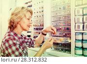 Купить «Mature glad woman customer picking various buttons», фото № 28312832, снято 23 мая 2019 г. (c) Яков Филимонов / Фотобанк Лори