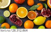 Купить «close up of citrus fruits on stone table», видеоролик № 28312864, снято 8 апреля 2018 г. (c) Syda Productions / Фотобанк Лори