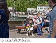 Купить «В парке Сокольники в День Победы мальчик дарит гвоздику ветерану ВОВ - сидящей на скамье нарядной пожилой женщине с медалями на груди», фото № 28316256, снято 9 мая 2016 г. (c) Наталья Николаева / Фотобанк Лори