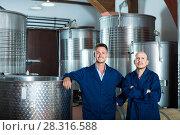 Купить «Two cheerful men in uniforms standing in winery fermentation compartment», фото № 28316588, снято 15 сентября 2019 г. (c) Яков Филимонов / Фотобанк Лори