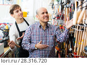 Купить «Young salesman helping client to select hammer», фото № 28316720, снято 19 ноября 2018 г. (c) Яков Филимонов / Фотобанк Лори