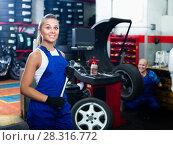 Купить «female technician standing with wheel balancing machinery at auto workshop», фото № 28316772, снято 19 сентября 2019 г. (c) Яков Филимонов / Фотобанк Лори
