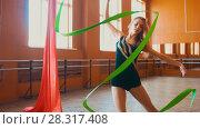 Купить «Young attractive woman trains with a green ribbon - gymnastics exercise in studio with mirror», иллюстрация № 28317408 (c) Константин Шишкин / Фотобанк Лори