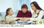 Купить «Smiling young woman with little girl helping elderly mother with paperwork at home», видеоролик № 28319312, снято 27 ноября 2017 г. (c) Яков Филимонов / Фотобанк Лори