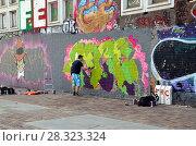 Купить «Райтер расписывает стену. Амстердам, Голландия», фото № 28323324, снято 8 апреля 2018 г. (c) Светлана Колобова / Фотобанк Лори