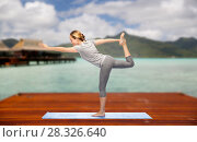 woman making yoga lord of the dance pose outdoors. Стоковое фото, фотограф Syda Productions / Фотобанк Лори