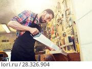 Купить «carpenter working with saw and wood at workshop», фото № 28326904, снято 14 мая 2016 г. (c) Syda Productions / Фотобанк Лори