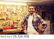 Купить «happy young workman in checkered shirt at workshop», фото № 28326908, снято 14 мая 2016 г. (c) Syda Productions / Фотобанк Лори