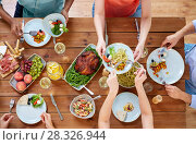 Купить «group of people eating at table with food», фото № 28326944, снято 5 октября 2017 г. (c) Syda Productions / Фотобанк Лори