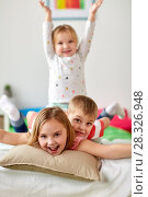 Купить «happy little kids having fun in bed at home», фото № 28326948, снято 15 октября 2017 г. (c) Syda Productions / Фотобанк Лори