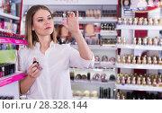 Купить «Girl choosing new nail polishes in cosmetics store», фото № 28328144, снято 31 января 2018 г. (c) Яков Филимонов / Фотобанк Лори