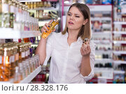 Купить «Girl with displeasure sniffing unpleasant smell of perfume», фото № 28328176, снято 31 января 2018 г. (c) Яков Филимонов / Фотобанк Лори