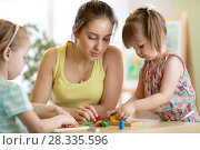 Children starring teacher play with educational toys, stack and arrange colorful pieces. Learning through experience concept, gross and fine motor skills. Стоковое фото, фотограф Оксана Кузьмина / Фотобанк Лори