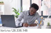 Купить «businessman with laptop and papers at office», видеоролик № 28338148, снято 19 апреля 2018 г. (c) Syda Productions / Фотобанк Лори