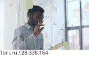 Купить «businessman with clipboard at office glass wall», видеоролик № 28338164, снято 19 апреля 2018 г. (c) Syda Productions / Фотобанк Лори