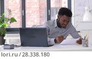 Купить «businessman with laptop and papers at office», видеоролик № 28338180, снято 19 апреля 2018 г. (c) Syda Productions / Фотобанк Лори