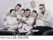 Купить «Smiling medical students and female professor taking selfie», фото № 28338608, снято 5 октября 2017 г. (c) Яков Филимонов / Фотобанк Лори
