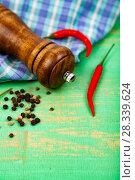Купить «Peppercorns, pepper mill, chili and a towel», фото № 28339624, снято 14 апреля 2018 г. (c) Елена Блохина / Фотобанк Лори
