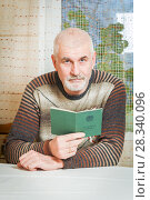A man retired reading his work book. Text in Russian: labor book. Мужчина держит трудовую книжку. Стоковое фото, фотограф Акиньшин Владимир / Фотобанк Лори