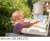 Купить «Small boy, toddler, 2 years old, blonde, in striped T-shirt washes his hands under washstand outdoors in countryside», фото № 28343272, снято 9 августа 2017 г. (c) Юлия Бабкина / Фотобанк Лори