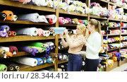 Купить «Portrait of two positive attractive girls choosing fabric among diversity on shelves in store», видеоролик № 28344412, снято 28 марта 2018 г. (c) Яков Филимонов / Фотобанк Лори
