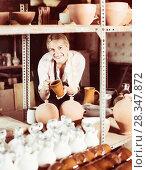 Купить «Positive woman carrying ceramic vessels», фото № 28347872, снято 6 декабря 2019 г. (c) Яков Филимонов / Фотобанк Лори