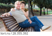 Купить «middleaged male and female posing on bench», фото № 28355392, снято 22 сентября 2017 г. (c) Татьяна Яцевич / Фотобанк Лори