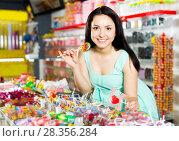 Купить «Woman posing to photographer with lollypop», фото № 28356284, снято 25 апреля 2017 г. (c) Яков Филимонов / Фотобанк Лори
