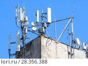 Купить «Антенны базовой станции оператора сотовой связи на крыше здания», фото № 28356388, снято 1 мая 2018 г. (c) Алексей Букреев / Фотобанк Лори