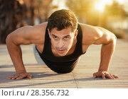 Купить «Sporty man doing push-ups outdoors», фото № 28356732, снято 14 августа 2017 г. (c) Яков Филимонов / Фотобанк Лори