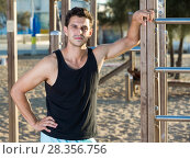 Купить «Sporty man near outdoor wall bars», фото № 28356756, снято 14 августа 2017 г. (c) Яков Филимонов / Фотобанк Лори