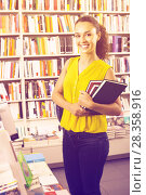 Купить «Happy woman reader holding books in bookstore», фото № 28358916, снято 23 мая 2019 г. (c) Яков Филимонов / Фотобанк Лори