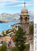 Montenegro. Kotor. A lot of tourists climb the Old Town Road uphill to visit beautiful 15th-century Church of Our Lady of Remedy (Crkva Gospa od Zdravlja) and admire the beautiful city of Kotor and Kotor Bay from above (2016 год). Редакционное фото, фотограф Виктория Катьянова / Фотобанк Лори