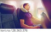 Купить «young man sleeping in plane with travel pillow», фото № 28363376, снято 21 октября 2015 г. (c) Syda Productions / Фотобанк Лори