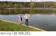 Купить «Moscow, Russia - May 02. 2018. man and woman are fishing in pond», видеоролик № 28368252, снято 2 мая 2018 г. (c) Володина Ольга / Фотобанк Лори