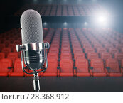 Vintage microphone on the stage of concert hall or theater with red seats and spot light. Стоковое фото, фотограф Maksym Yemelyanov / Фотобанк Лори