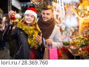 Купить «young couple in Christmas hat buying decoration at fair», фото № 28369760, снято 14 декабря 2017 г. (c) Яков Филимонов / Фотобанк Лори