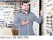 Купить «young male seller assisting woman in choosing door handles in shop», фото № 28369780, снято 5 апреля 2017 г. (c) Яков Филимонов / Фотобанк Лори
