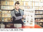 Купить «Adult male seller demonstrating assortment», фото № 28369796, снято 5 апреля 2017 г. (c) Яков Филимонов / Фотобанк Лори