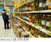Moscow, Russia - April 14. 2018. buyer chooses sunflower oil in the Auchan store. Редакционное фото, фотограф Володина Ольга / Фотобанк Лори