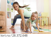 Купить «Young mother playing twister with her kids. Cheerful family at home. Happy family playing together», фото № 28372648, снято 25 апреля 2019 г. (c) Оксана Кузьмина / Фотобанк Лори