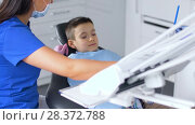 Купить «female dentist with kid patient at dental clinic», видеоролик № 28372788, снято 26 апреля 2018 г. (c) Syda Productions / Фотобанк Лори